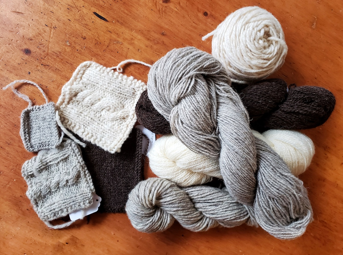Several skeins of wool yarn and swatches knitted from the yarn.